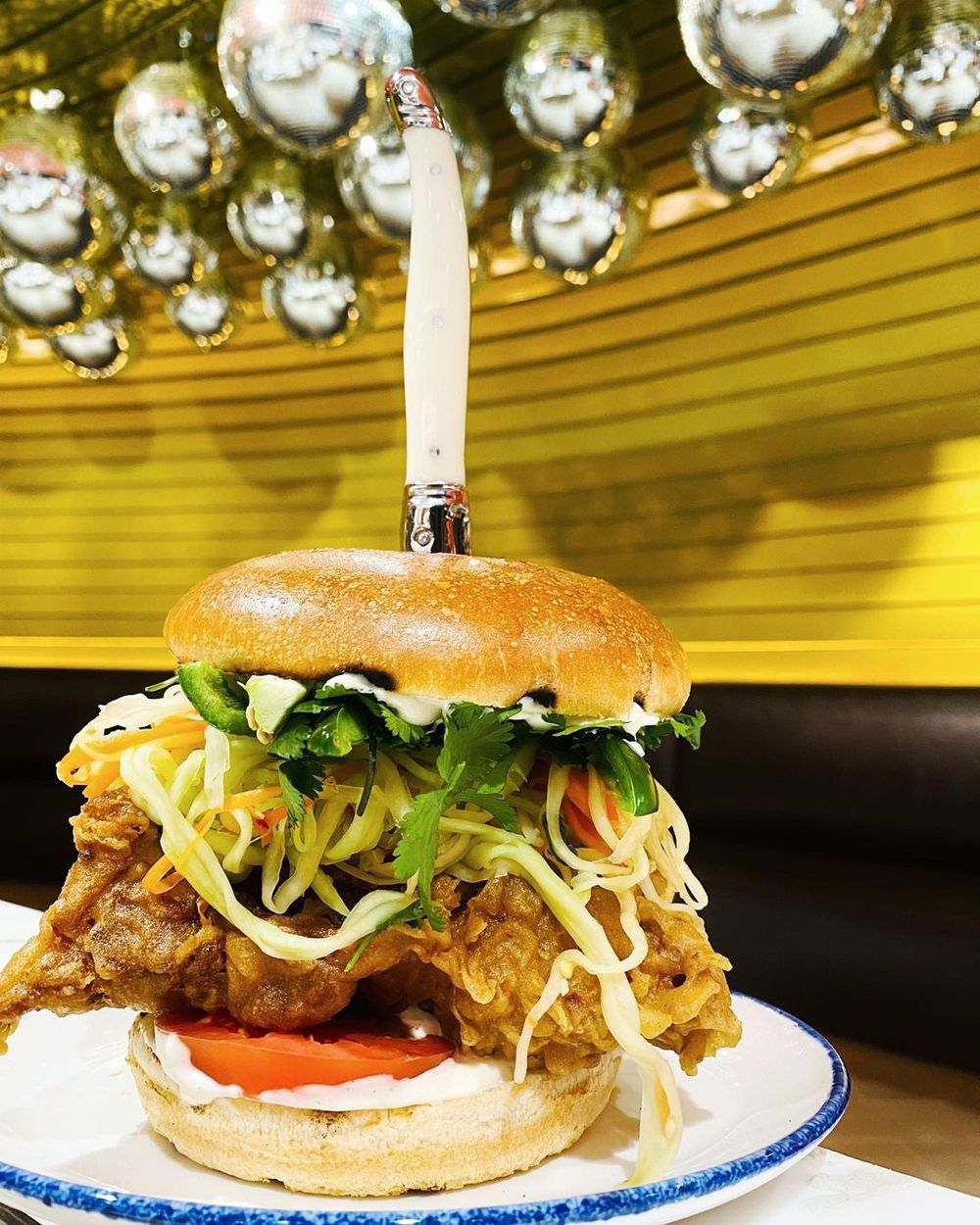Fried chicken sandwich with a knife in the center