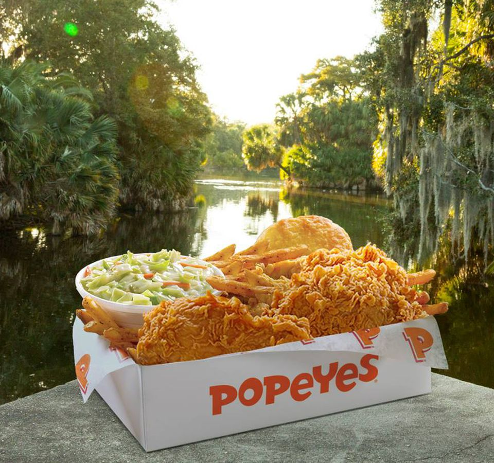 A Popeyes box filled with fried chicken, coleslaw, and a biscuit is set against a swamp-like backdrop