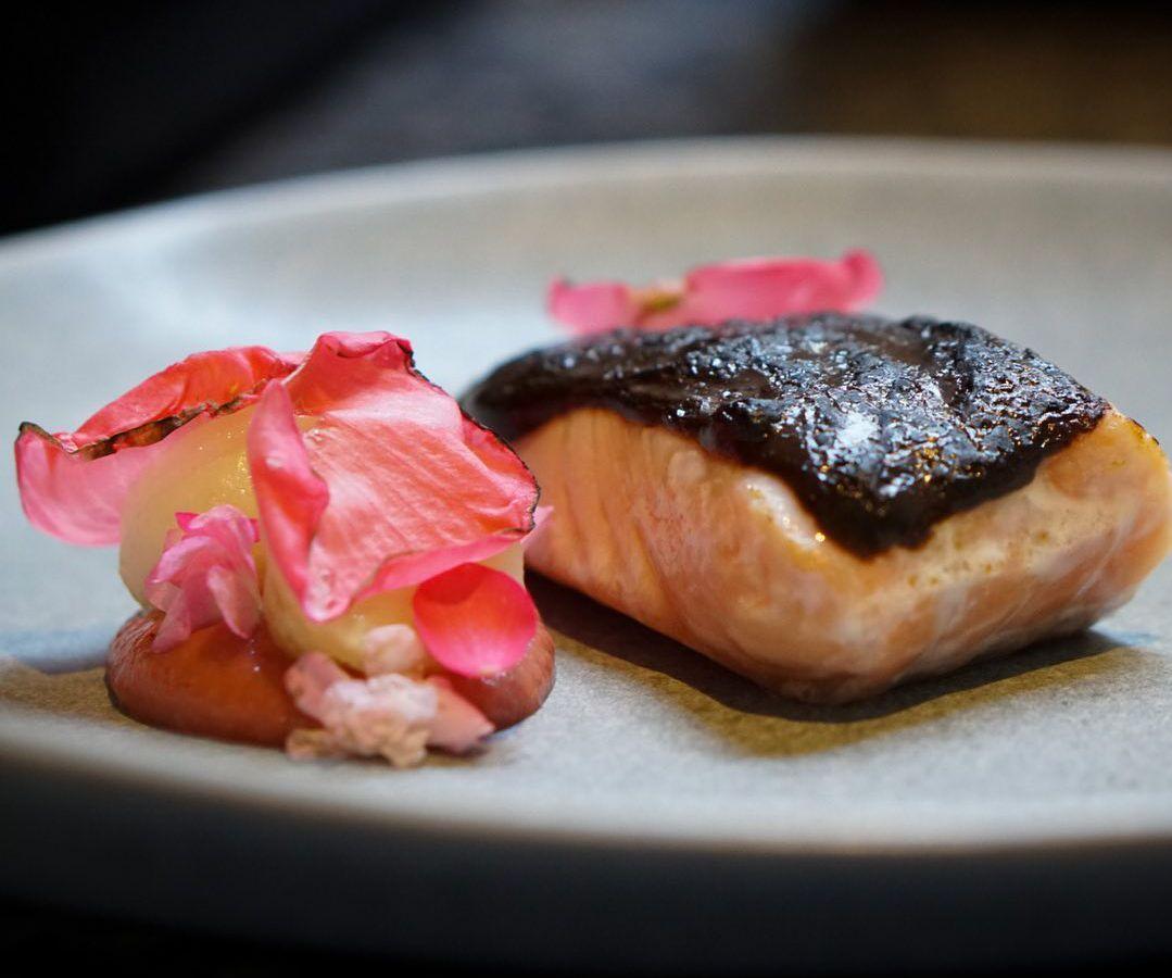 Salmon, miso, turnip, kohlrabi, begonia, and strawberry on a plate