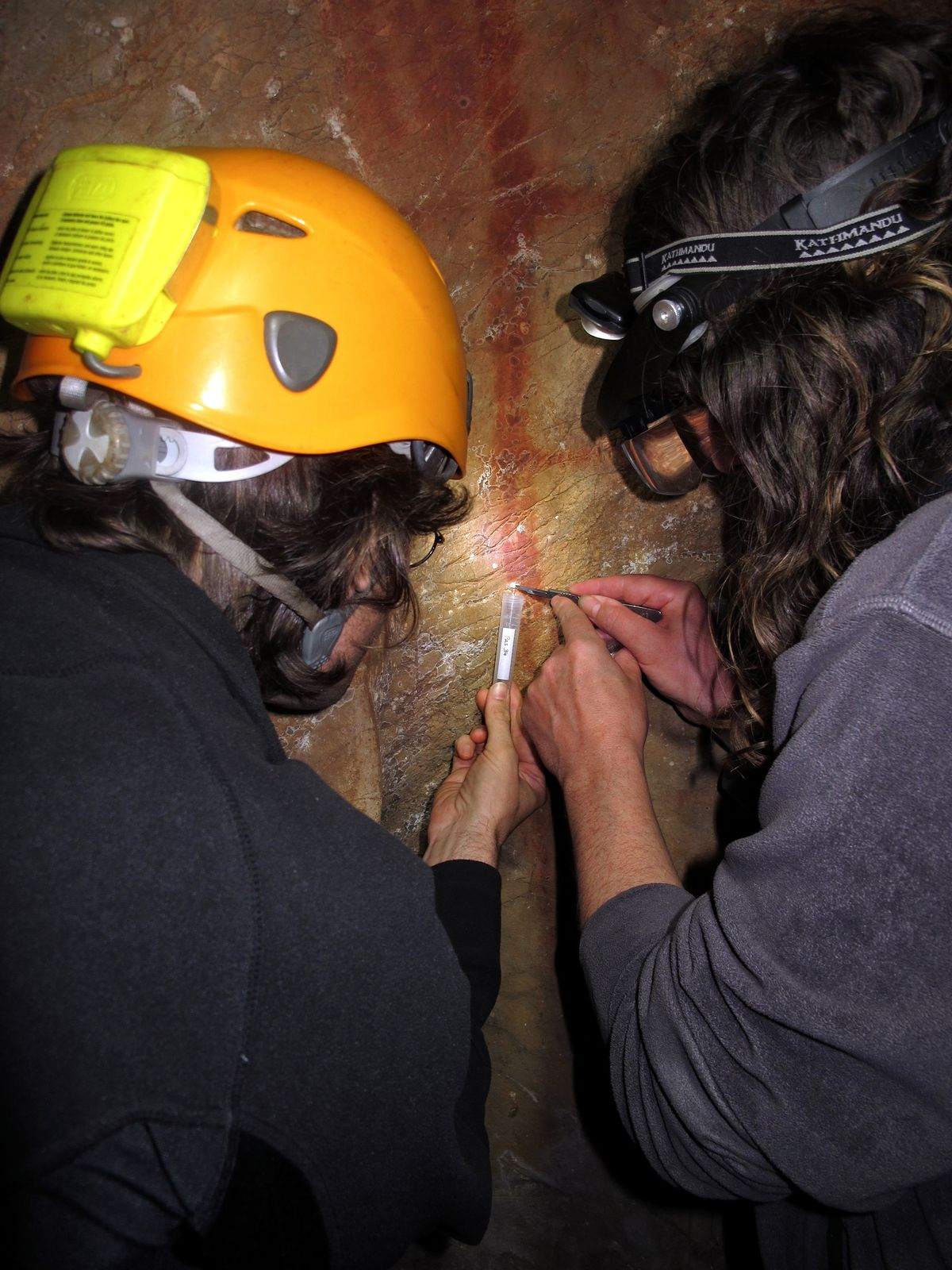 Dirk Hoffmann and Alistair Pike scraping cave crust from above a ladder-like painting thought to have been created by Neanderthals.