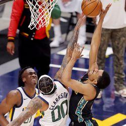 Utah Jazz guard Jordan Clarkson (00) blocks Memphis Grizzlies guard De'Anthony Melton (0) as the Utah Jazz and the Memphis Grizzlies play in game one of their NBA playoff series at Vivint Arena in Salt Lake City on Sunday, May 23, 2021.