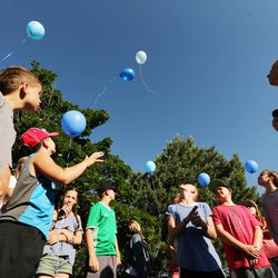 A group of kids release balloons as community members gather to tie ribbons and write messages to the Rackley family and first responders of the murder-suicide along Alta Canyon Drive in Sandy on Saturday, June 10, 2017.