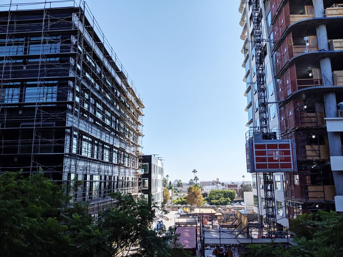 A photo of an under-construction duo of lower-rise buildings and the base of the taller tower.