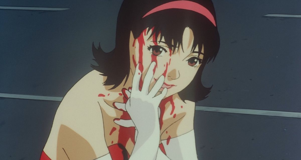 mima streaks blood down her face with a white glove, while staring directly at camera