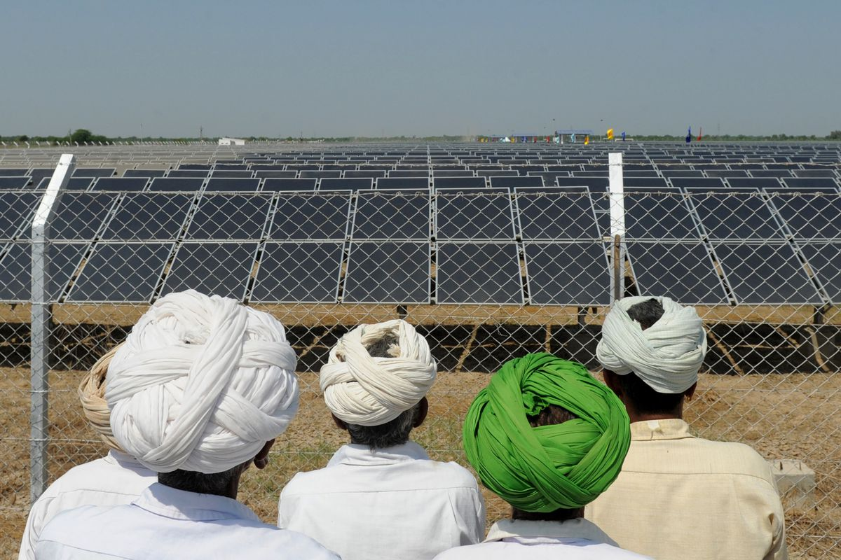 Indian villagers look at solar panels during the inauguration of a solar farm in the village of Gunthawada, Banaskantha district, some 175kms. from Ahmedabad on October 14, 2011.