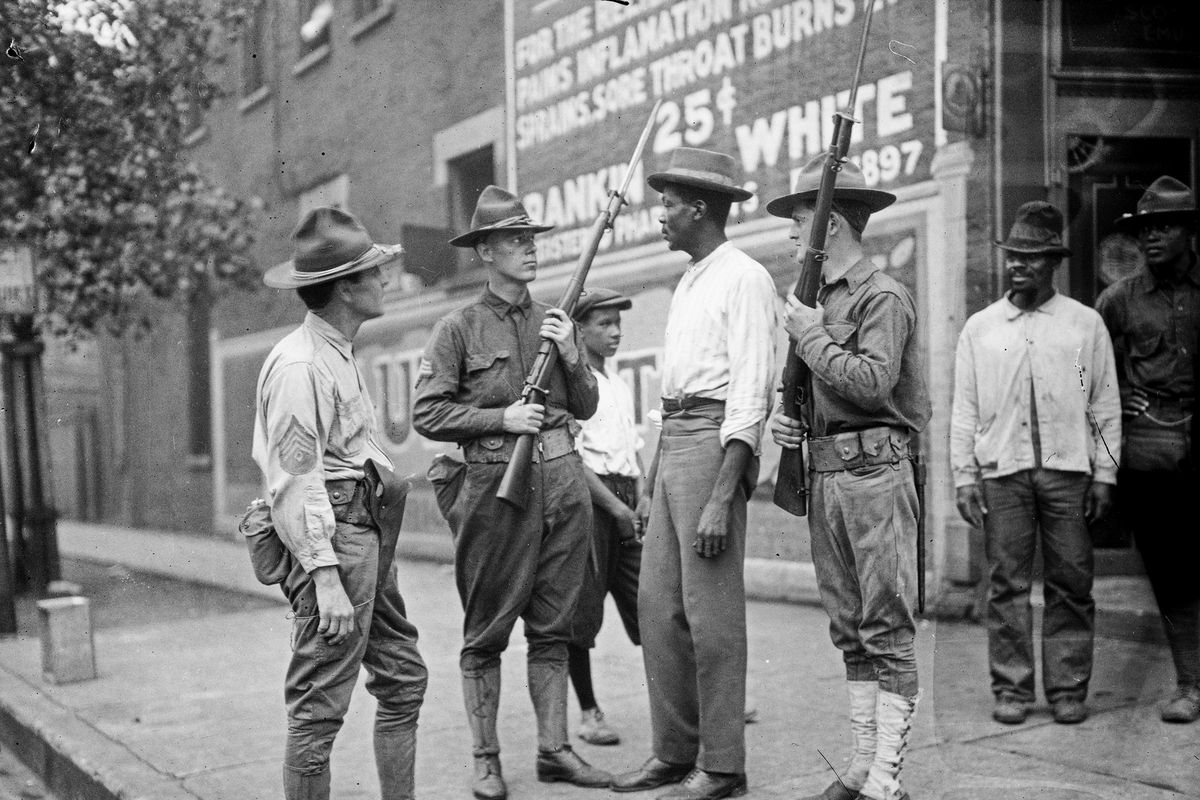 Armed National Guardsmen and African American men stand on a sidewalk during the 1919 race riots in Chicago.