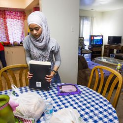 Nour Bilal, 15, puts away her homework while her mom, Kholoud Abou Arida, prepares dinner and her brother, Zain Bilal, 3, plays at their home in Millcreek on Tuesday, Sept. 8, 2015.