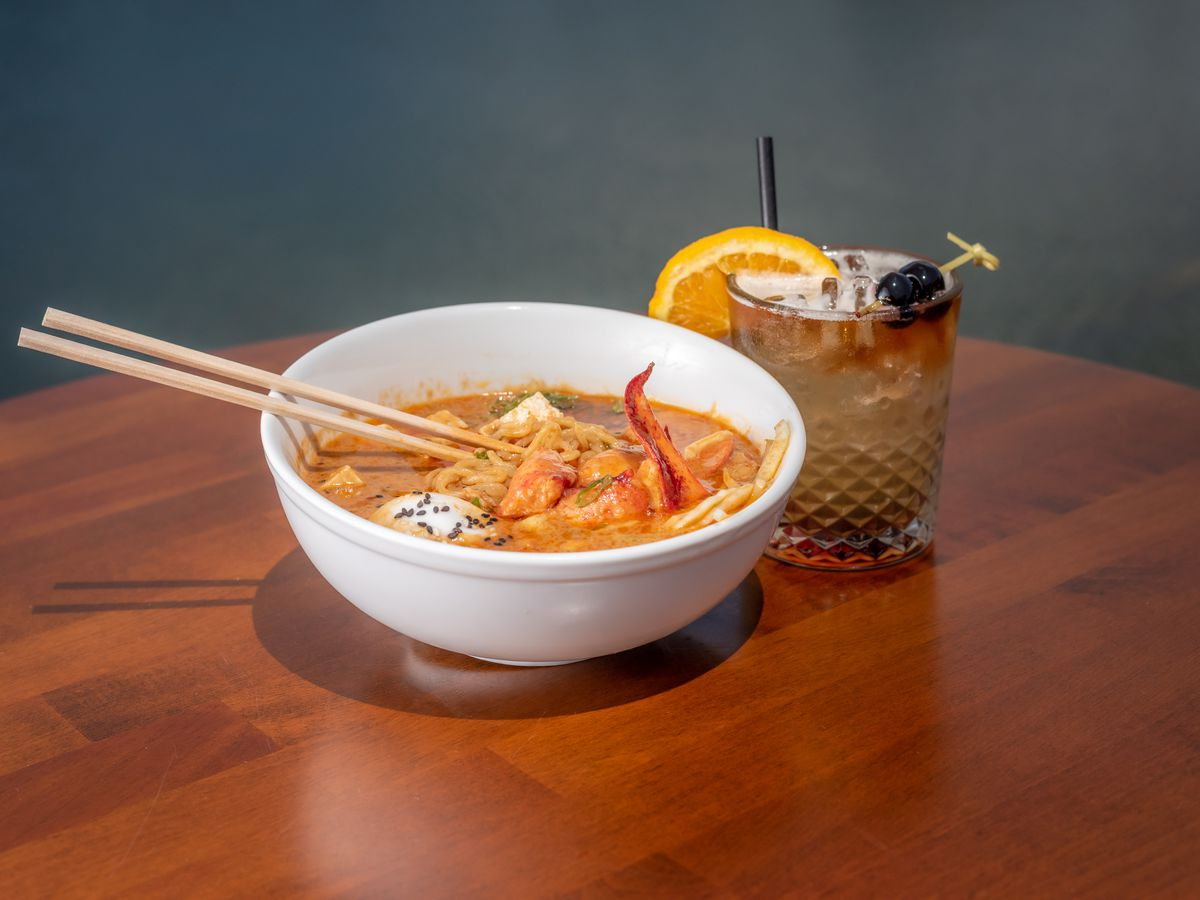 Chopsticks rest on a white bowl of ramen with lobster in a brown broth that sits on a wooden table