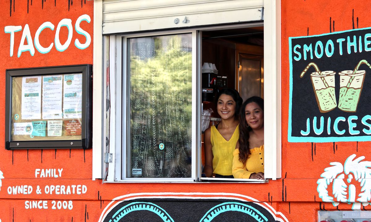Two sisters peek out from the open window of their takeaway taqueria, colored orange, in Austin, Texas.