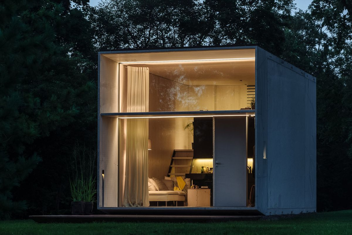 A concrete block home at night lit from within with a huge glass expanse making up the front of the home showing an open-plan living room and kitchen area and stairs leading up to a sleeping loft.