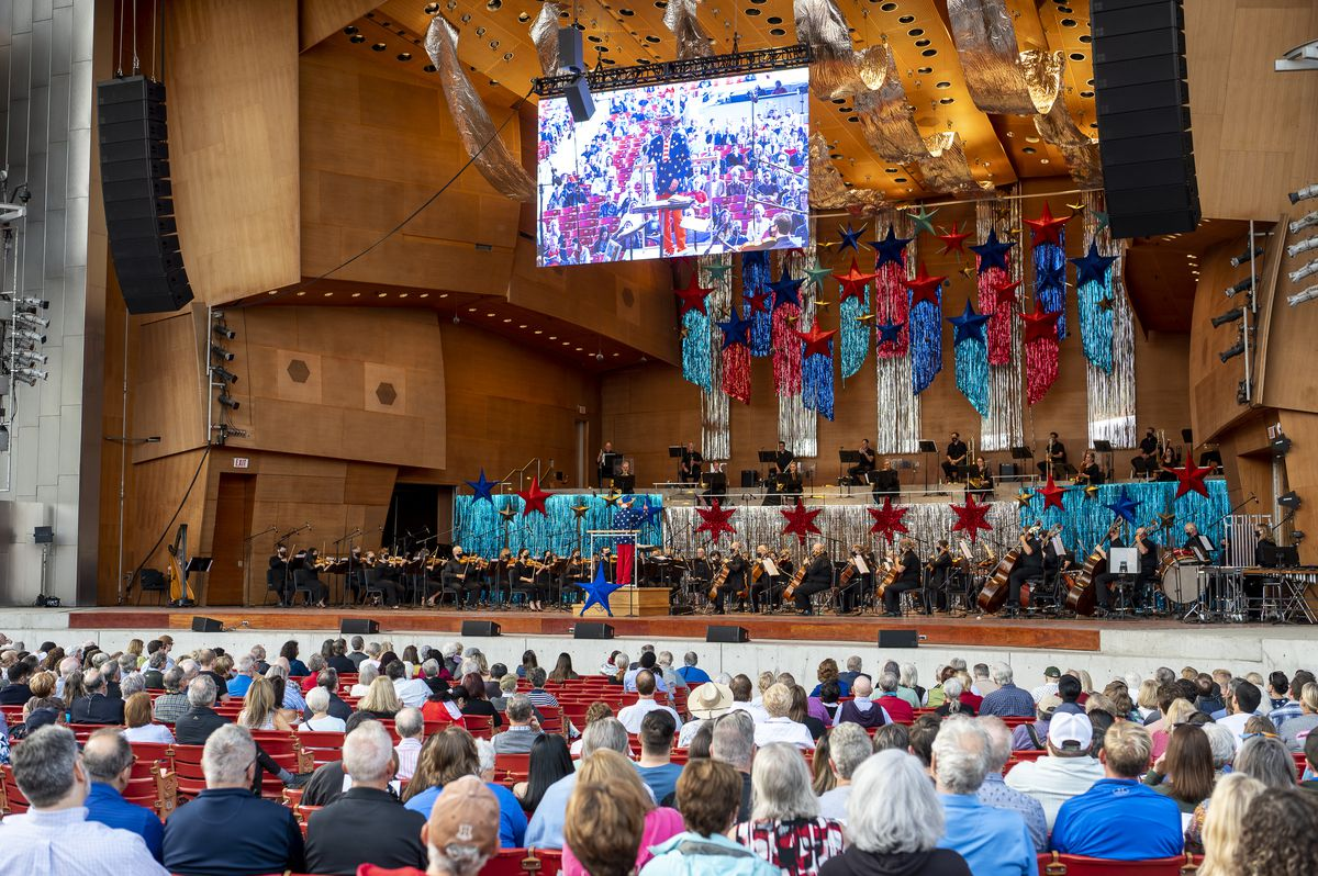 Concertgoers listen to the Grant Park Orchestra performing at the Pritzker Pavilion during the Grant Park Music Festival at Millennium Park, Friday night.
