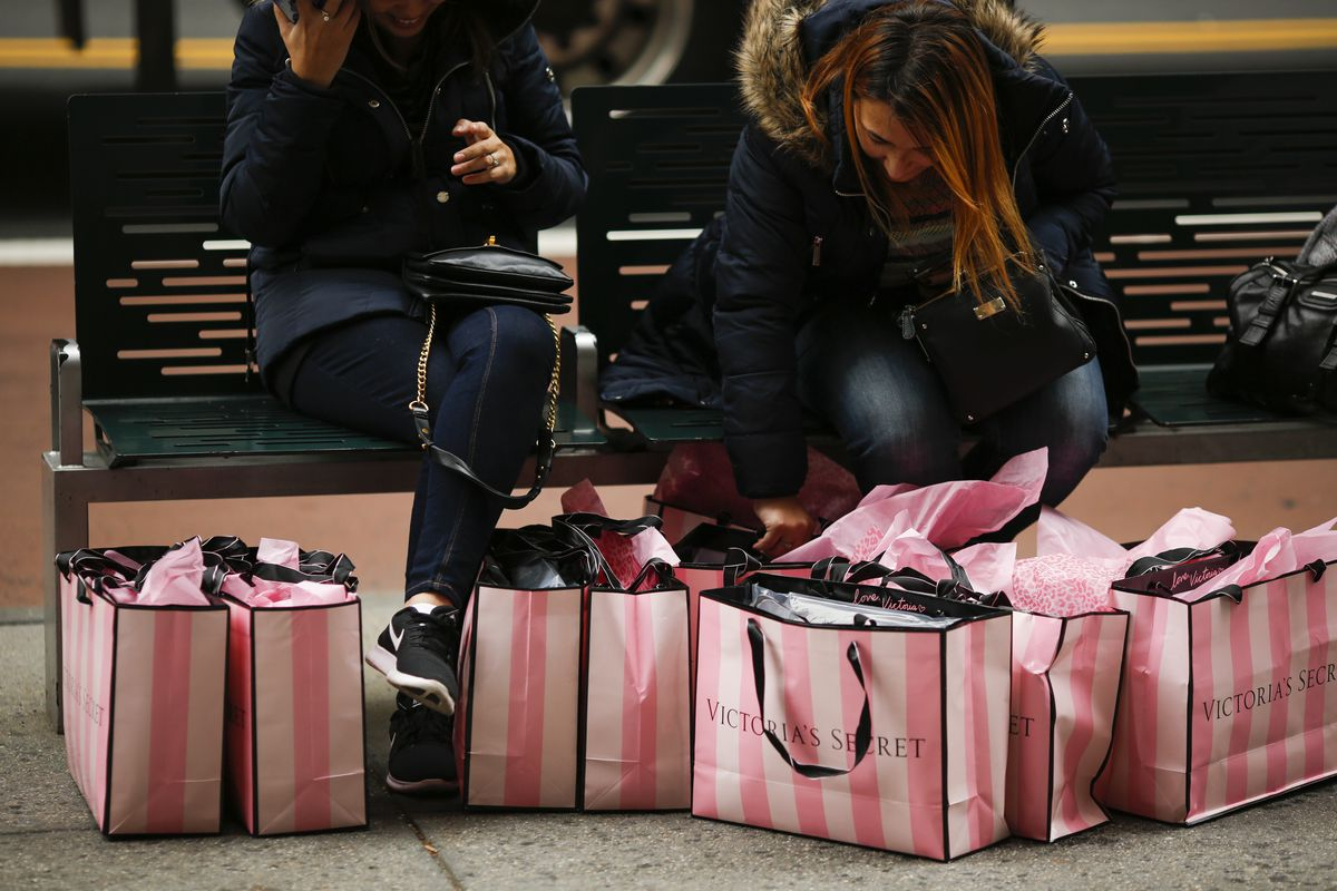 Women sit on a bunch with numerous Victoria's Secret bags at their feet.