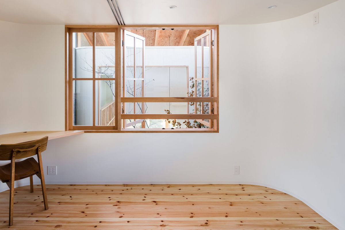 Room with wood floors, plain white walls, and a window overlooking open space below.