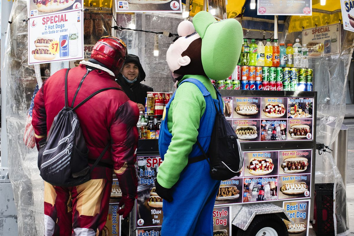 Two costumed characters wait to get food at a hot dog stand.