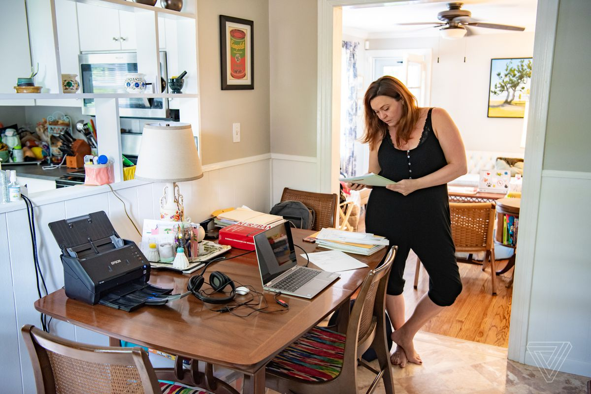 Sarah Owings stands at a table and work desk in her home.