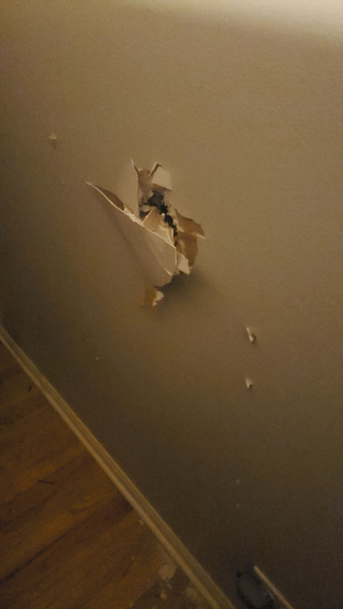 The hole in Dave Papish and Ashley Holmes' bedroom wall caused by a claw hammer from the neighboring unit.
