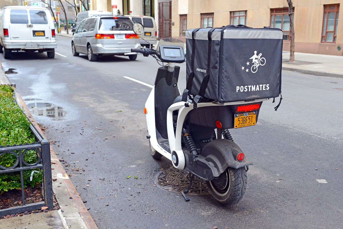 A motorbike parked on the street with a Postmates delivery bag attached to the back.