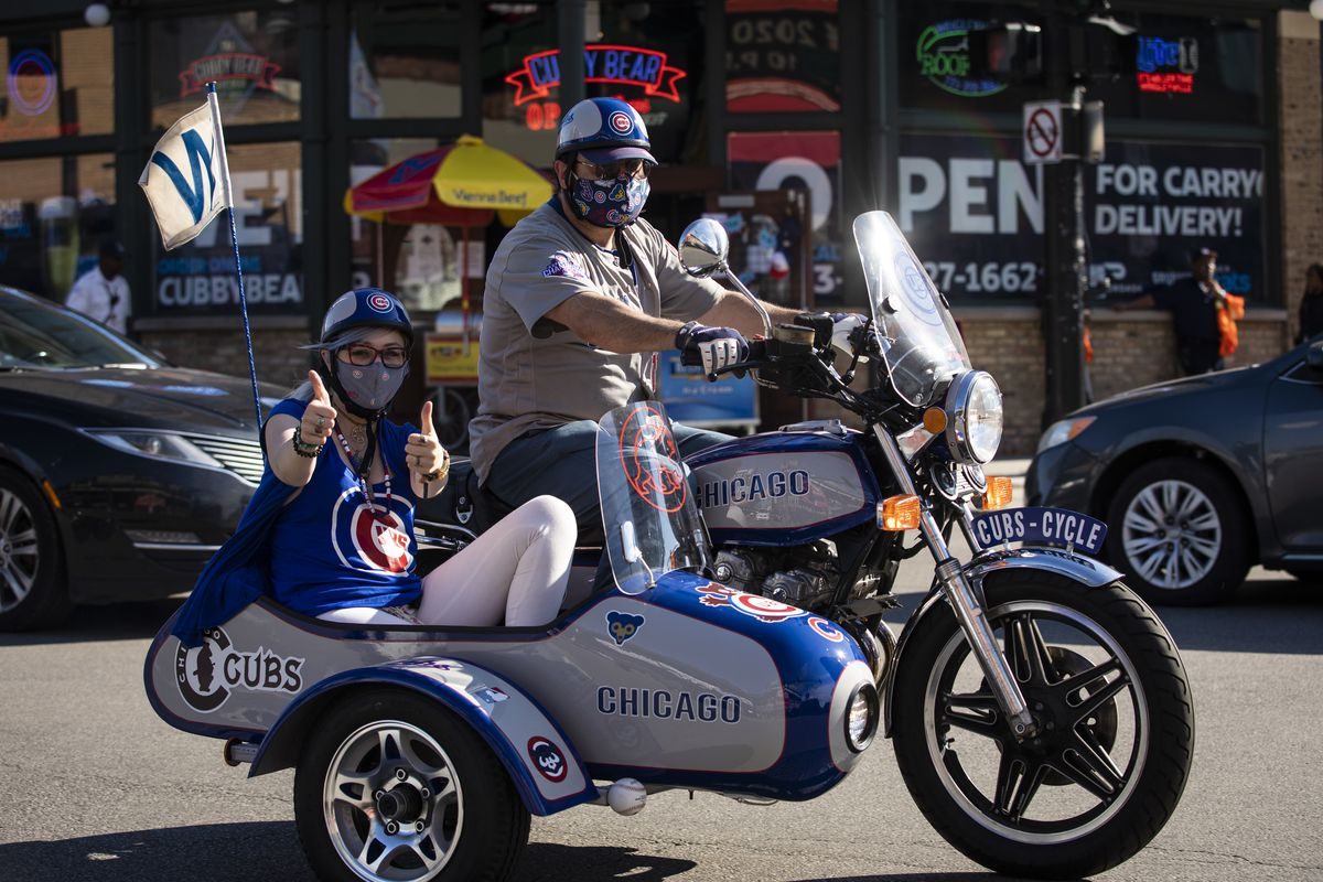 Fans drive by Wrigley Field shortly before the start of the opening day game between the Chicago Cubs and the Milwaukee Brewers, Friday evening, July 24, 2020.