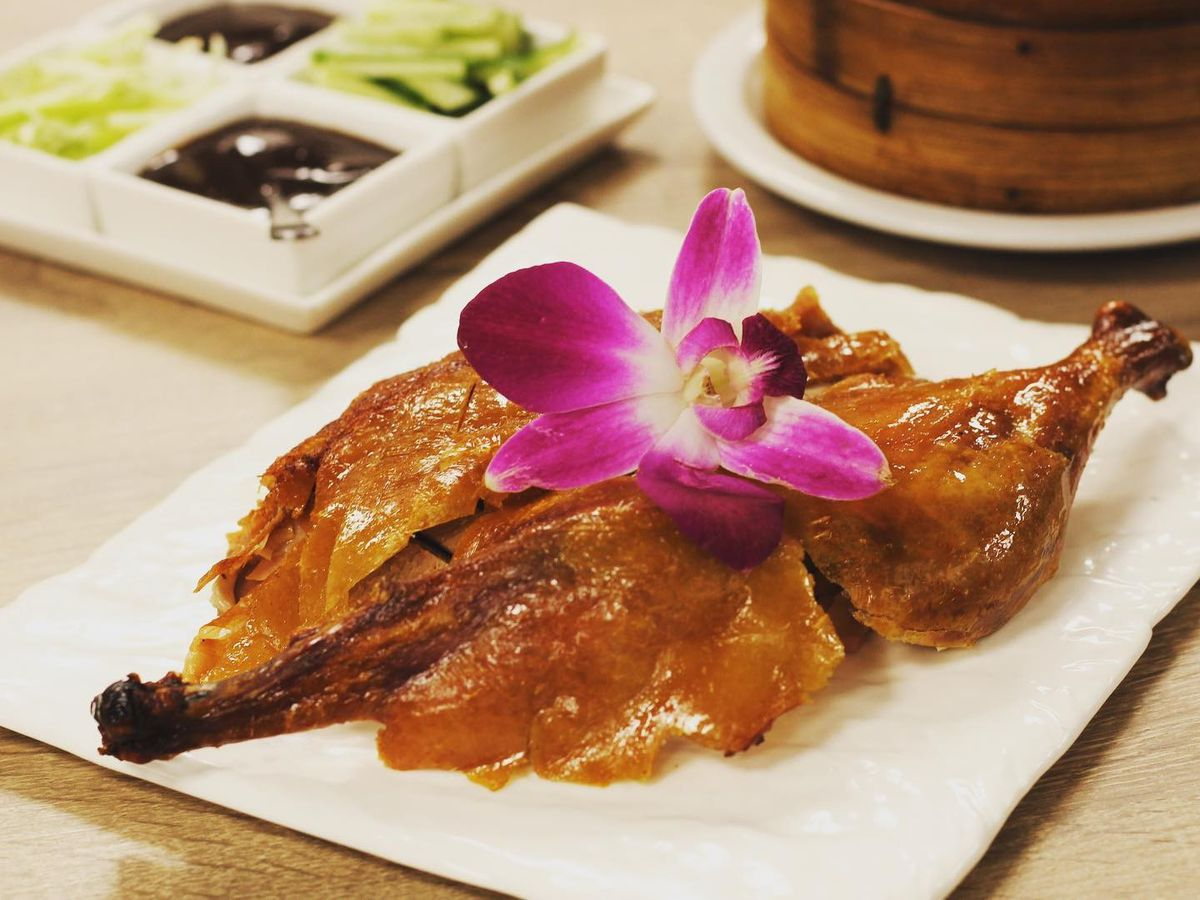 Pieces of peking duck beneath crackly skin garnished with a bright pink flower, on a table beside a steamer basket and dipping sauces