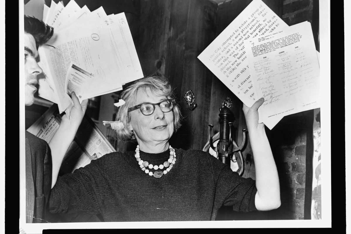 Black and white archival photo of a woman in glasses holding up documents.