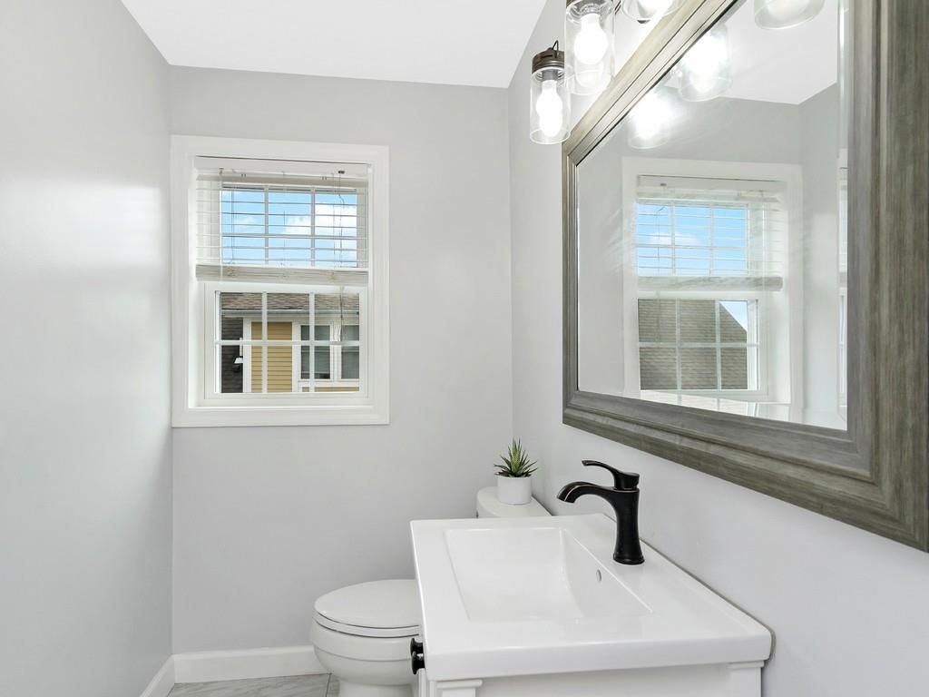 A bathroom with a toilet and a sink but no shower or tub.