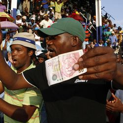 Miners sing and dance whilst holding South African bank notes in Lonmin Platinum Mine near Rustenburg, South Africa, Tuesday, Sept. 18, 2012. Striking miners have accepted a company offer of a 22% overall pay increase to end more than five weeks of crippling and bloody industrial action.