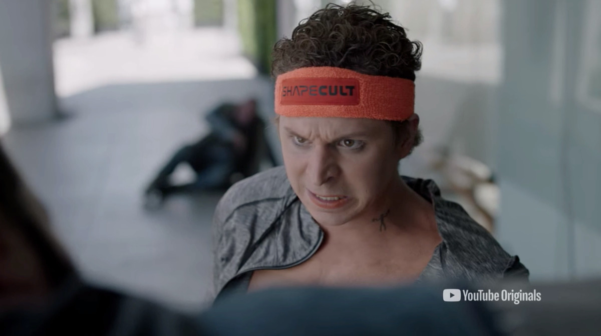 """Still of 'Weird City' featuring Michael Cera cringing, as well as sporting a neck tattoo and an orange sweatband reading """"ShapeCult"""""""