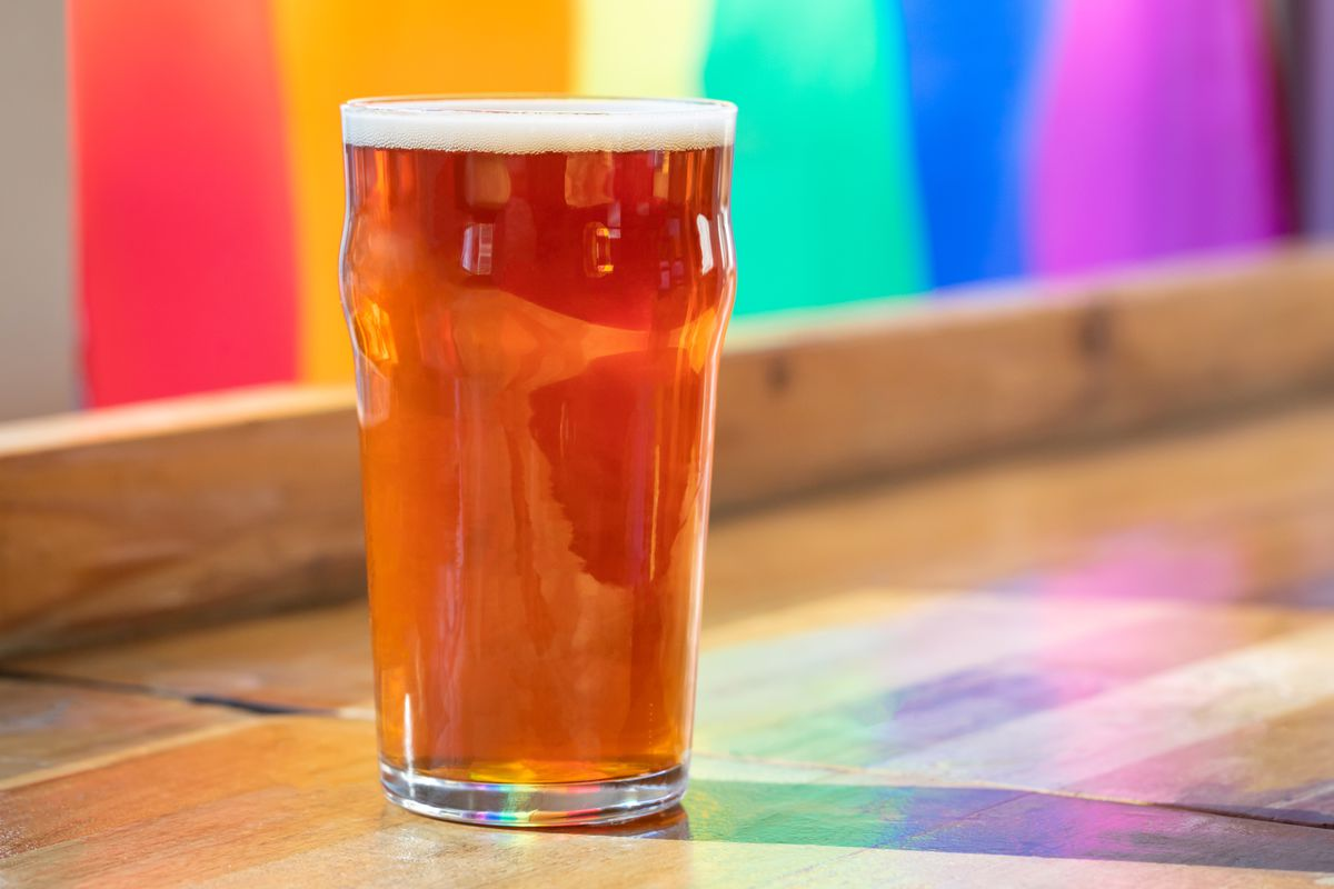A glass of beer sits on a counter in front of a rainbow flag