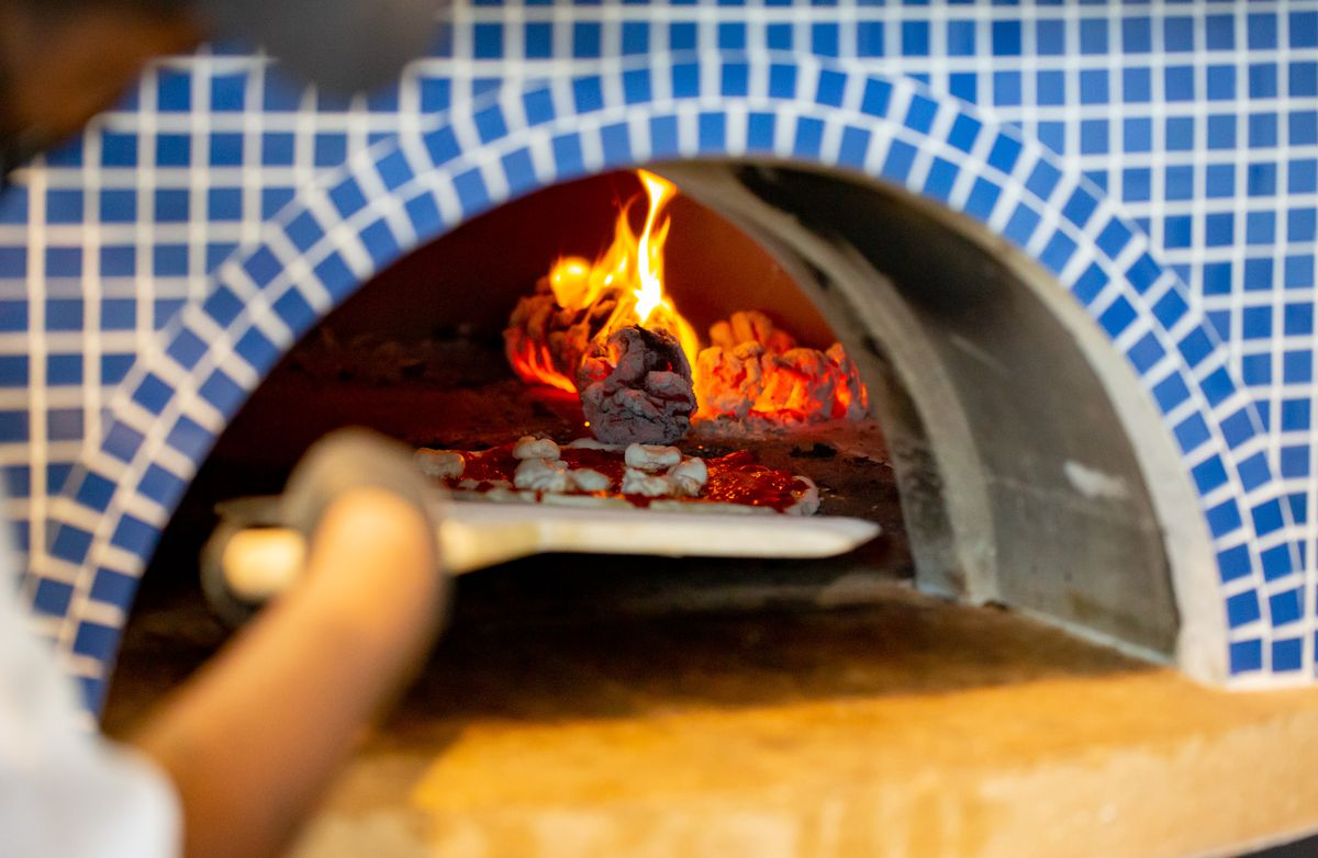 Bright blue and white tiled brick pizza oven is lit with orange flames as a pizza is slide into the oven to bake