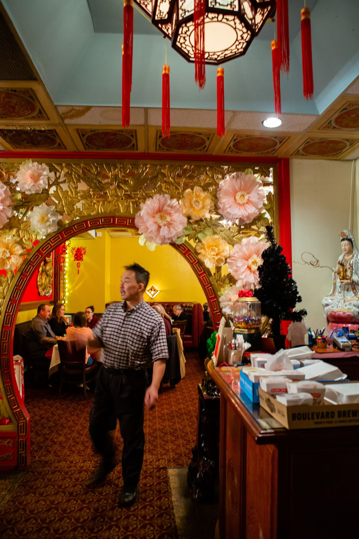 Man stands under curved archway in a Chinese restaurant.