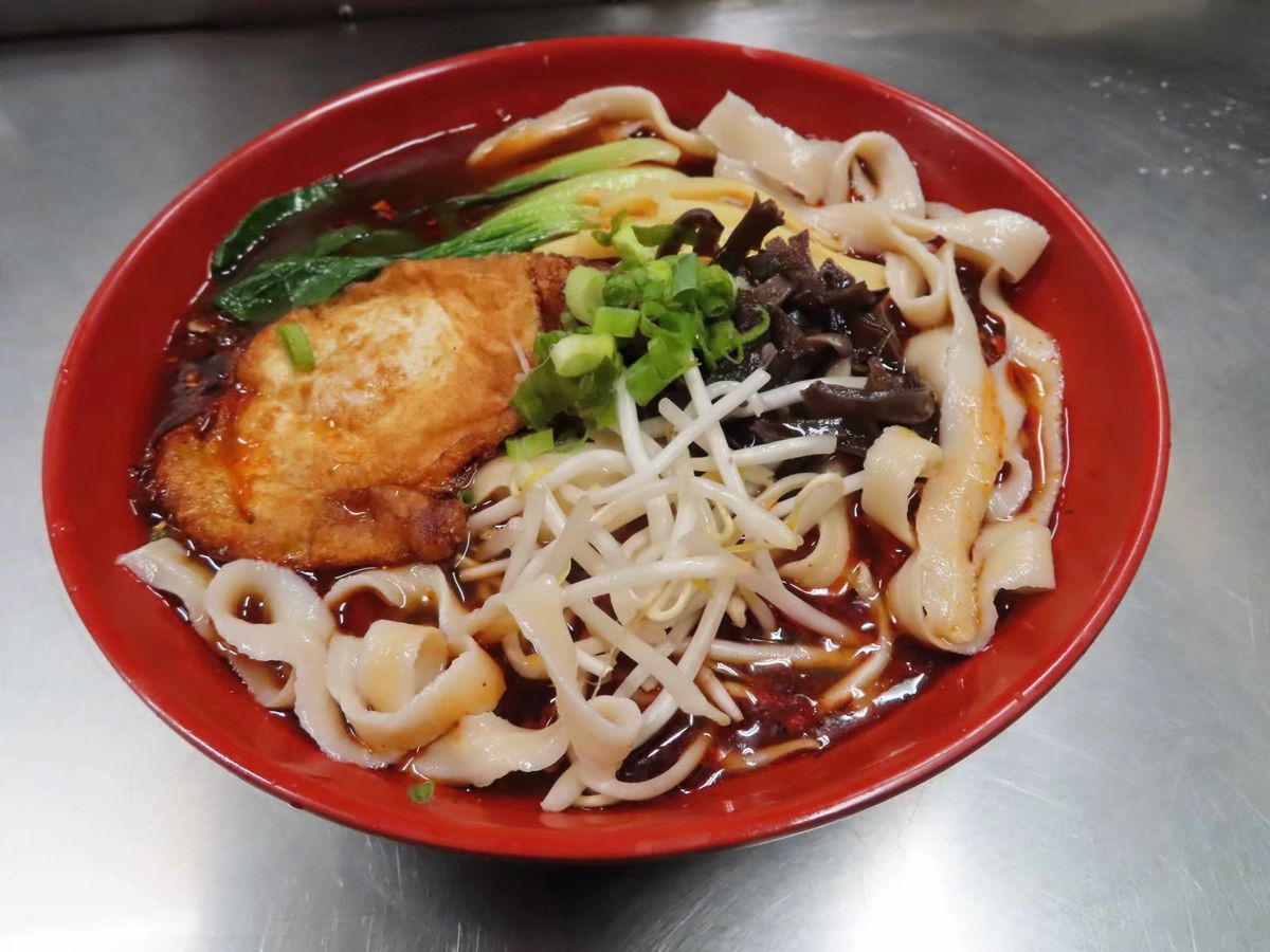 Bowl of noodle soup topped with bean sprouts and greens