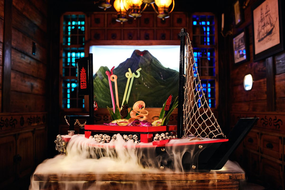 A large toy ship with cocktail garnishes on it and colorful straws and steam pouring off the deck