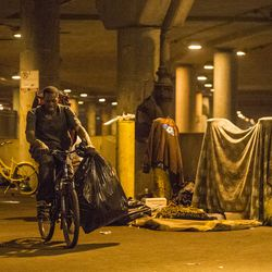 """A homeless man who lives in """"The Triangle"""" hauls away a bag of his belongings to his new camp in lieu of the deadline that residents of this part of Lower Wacker Drive were given to evacuate the area by the city of Chicago, Monday, June 11, 2018, in Chicago. 