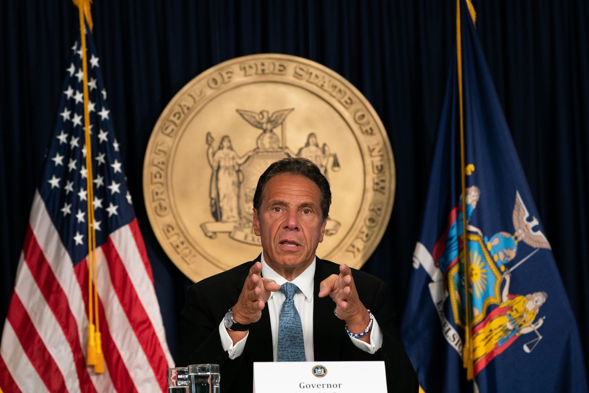 New York Governor Cuomo sits in front of the state seal and the American flag during a briefing