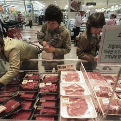 """South Korean shoppers watch to buy  domestic and Australian beef on the shelves at a Lotte Mart store in Seoul, South Korea, Wednesday, April 25, 2012. Two major South Korean retailers, including Lotte Mart,  suspended sales of U.S. beef Wednesday following the discovery of mad cow disease in a U.S. dairy cow. Reaction elsewhere in Asia was muted with Japan saying there's no reason to restrict imports. The letters on a card read """" Starting from the 25th, we will temporarily stop the sales of the US beef. Thank you for your understanding""""."""