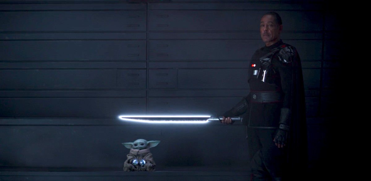 Moff Gideon holds his darksaber above Grogu aka Baby Yoda in The Mandalorian