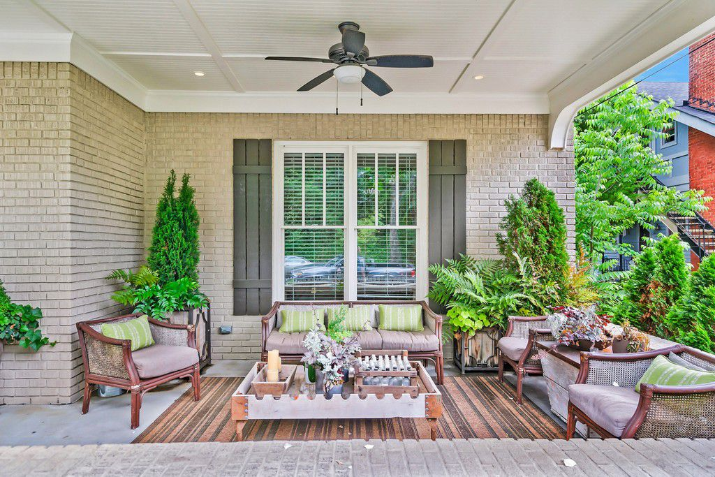 A porch with nice wooden chairs and a ceiling fan overhead and windows with shutters.