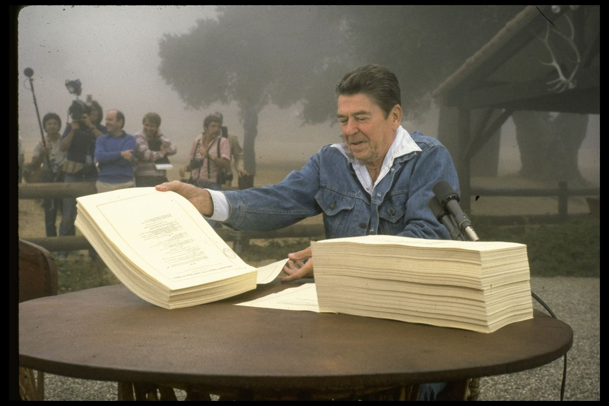President Ronald Reagan signs the Economic Recovery Tax Act of 1981, while on vacation at his ranch named Rancho del Cielo.