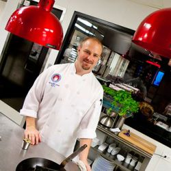 Executive chef (and not a student), Kris Jakob standing in front of a hydroponic herb garden in the kitchen.