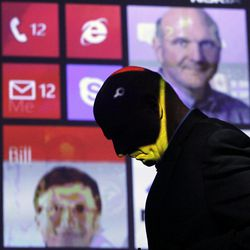 Steve Ballmer, CEO of Microsoft, walks past a projected display showing Bill Gates, lower left, and himself, during a discussion of Nokia's newest smartphone, the Lumia 920, equipped with Microsoft's Windows Phone 8, Wednesday, Sept. 5, 2012 in New York. Nokia revealed its first smartphones to run the next version of Windows Wednesday, a big step for a company that has bet its future on an alliance with Microsoft.