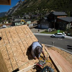 Carlos Aguiolar works on building a zero energy rhome in the Treseder at Little Cottonwood development in Sandy on Friday, Aug. 12, 2016. The development's model home, pictured in background, is featured in the Parade of Homes.