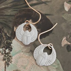"""<a href=""""http://ericaweiner.com/products/winged-scarab-earring#.UtAcm-y81EB"""">Winged scarab earrings</a>, $15.00 (were $25.00)"""