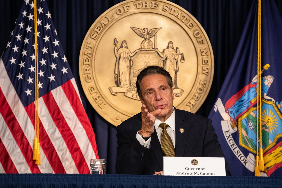 Gov. Cuomo speaks while seated at a table, in front of the American flag and seal of New York State.
