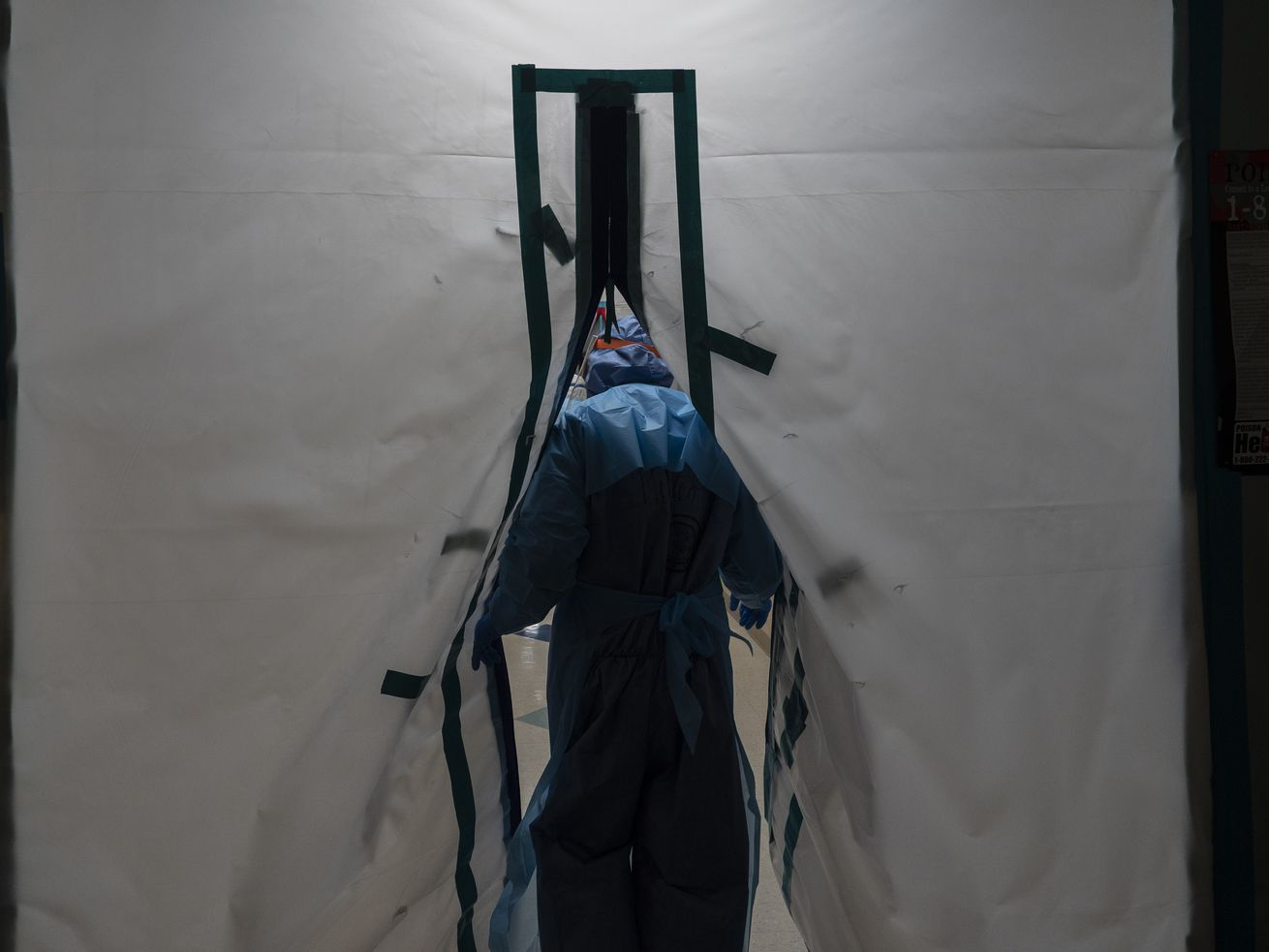 A hospital worker walks through a tented opening.