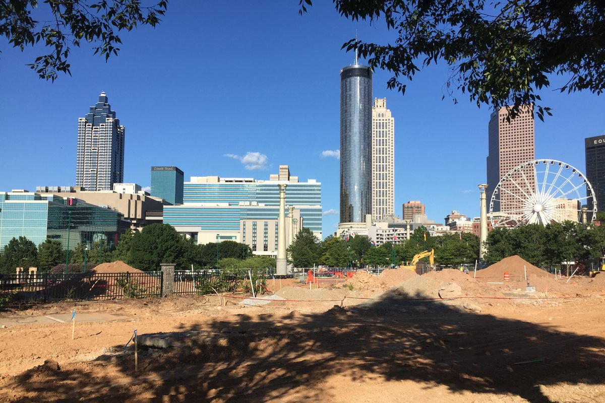 A massive construction site, with downtown skyline in the background.