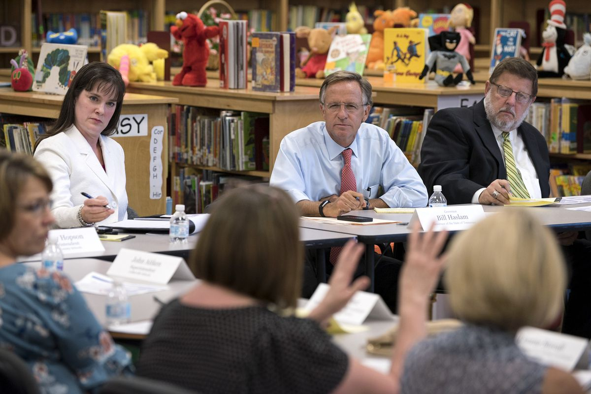 """Gov. Bill Haslam (center) listens to feedback of teachers, school administrators, and testing coordinators during an Aug. 30 roundtable session in Shelby County. His education commissioner, Candice McQueen (left) participated in all six roundtable gatherings, along with Wayne Miller (right), the retired chief of the state's superintentents association, who chaired Haslam's """"listening tour"""" advisory team."""