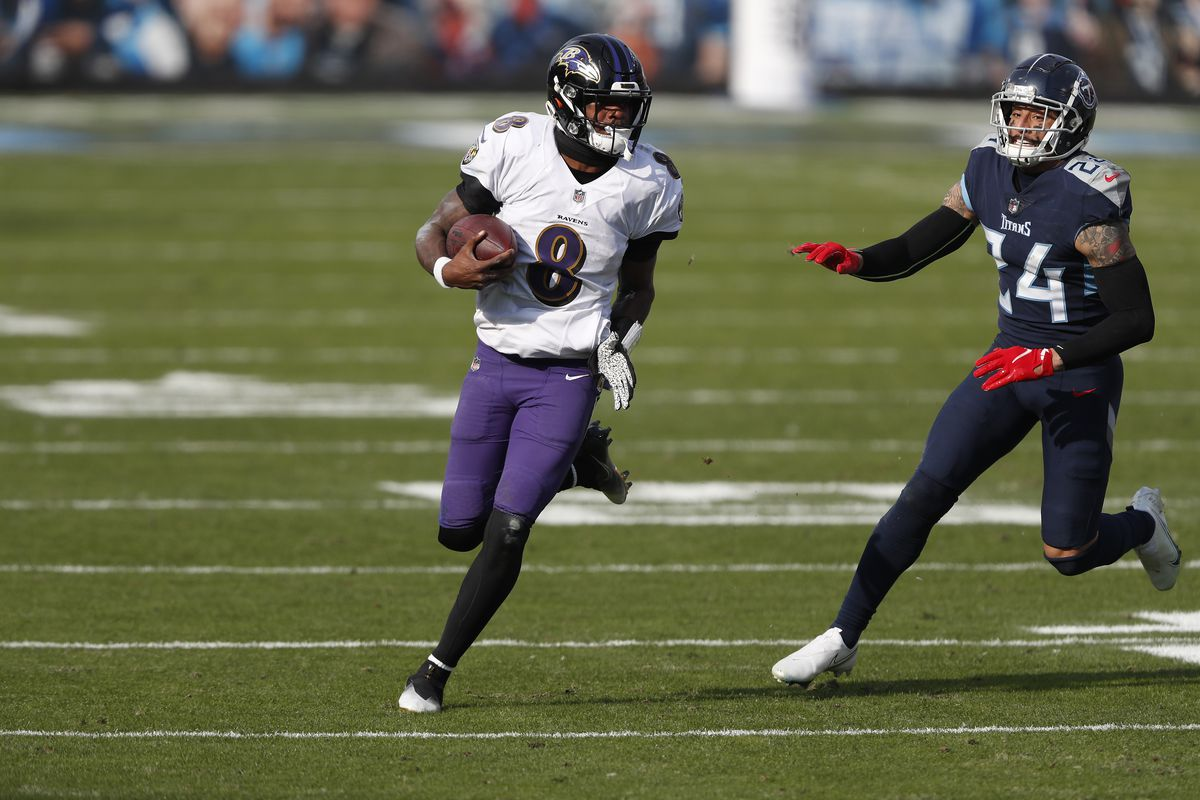 Quarterback Lamar Jackson #8 of the Baltimore Ravens carries the ball for yardage against safety Kenny Vaccaro #24 of the Tennessee Titans during the third quarter of their AFC Wild Card Playoff game at Nissan Stadium on January 10, 2021 in Nashville, Tennessee.