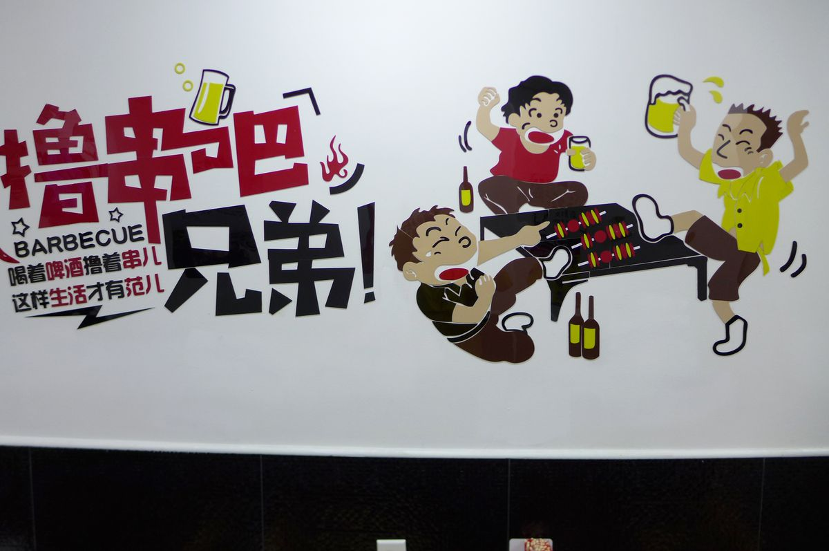 A colorful plastic mural shows customers dancing around a kebab grill.