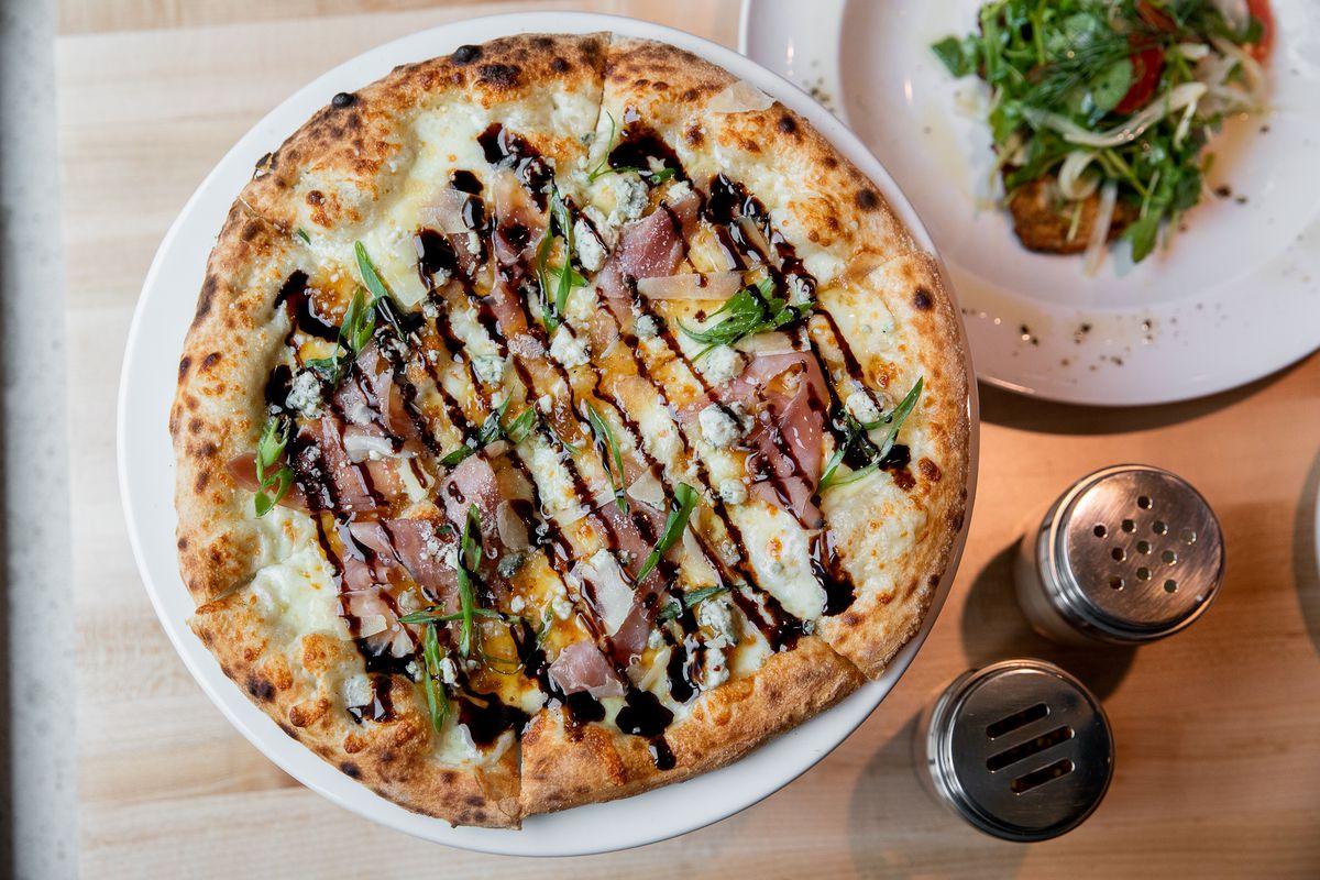 A whole, round pizza with prosciutto, arugula and a balsamic drizzle.