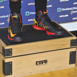 These are shoes. They are on the feet of the reigning rookie of the year. They are red and black and yellow.